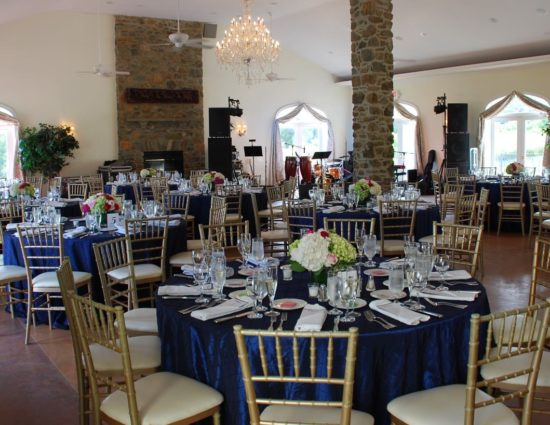 Large room set up for a wedding reception with navy tablecloths and white napkins