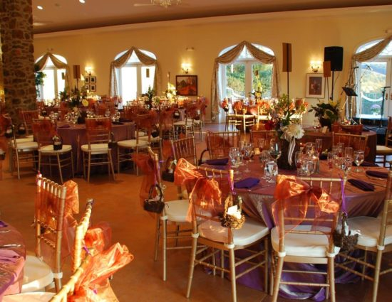 Large room set up for a wedding reception with pink sheer tablecloths and purple napkins