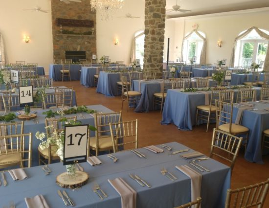Large room set up for a wedding reception with powder blue tablecloths and gray napkins