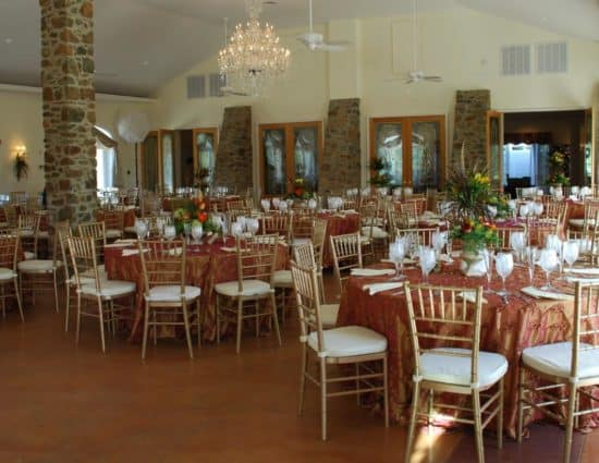 Large room set up for a wedding reception with gold and pink tablecloths and white napkins