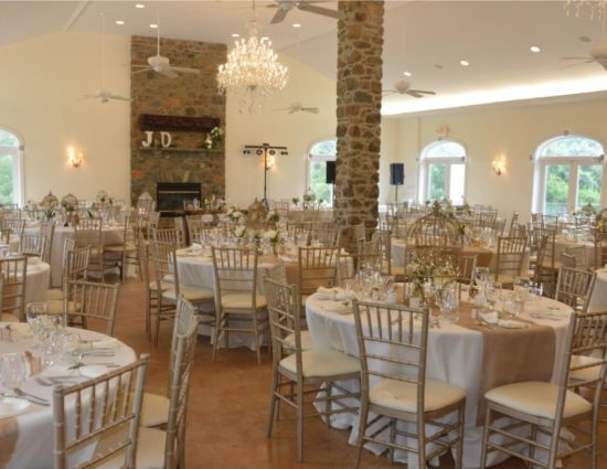 Large room set up for a wedding reception with white and burlap tablecloths