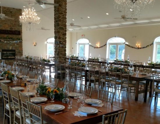 Large room set up with wooden tables and chairs for a large wedding reception