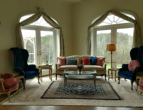 Large room with large area rug, blue and pink upholstered chairs, cream upholstered sofa, coffee table, and end tables