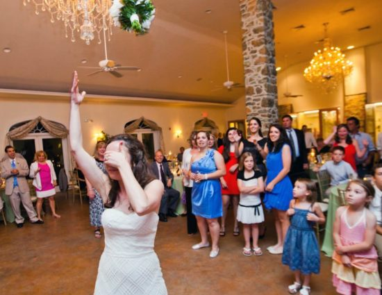 Bride in white dress throwing bouquet to group of ladies