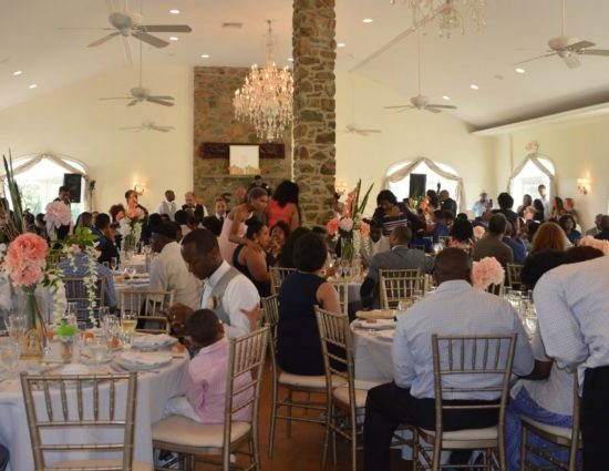Large room set up for a wedding reception with white tablecloths and napkins and people eating and talking