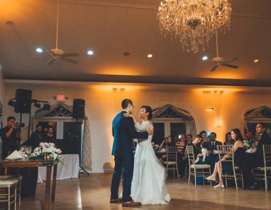 Bride in white dress and groom in dark blue suit enjoying their first dance while people watch