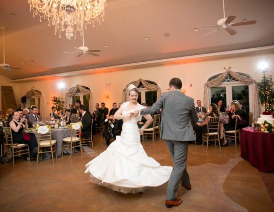 Bride in white dress and groom in gray suit enjoying their first dance while people watch