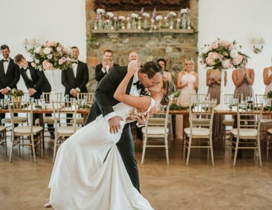 Bride in white dress and groom in black suit kissing with wedding party standing behind reception tables behind them