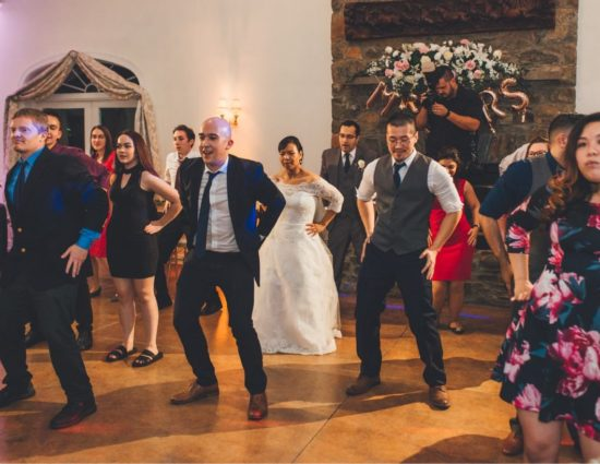 Group of wedding guests doing a line dance with the bride and groom
