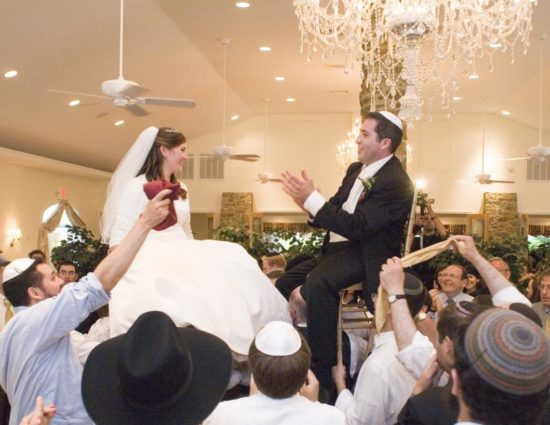 Bride in white dress and groom in black suit sitting on chairs raised in the air with many people celebrating around them