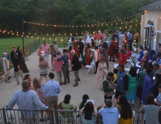 Large wedding party on concrete patio with people talking to each other