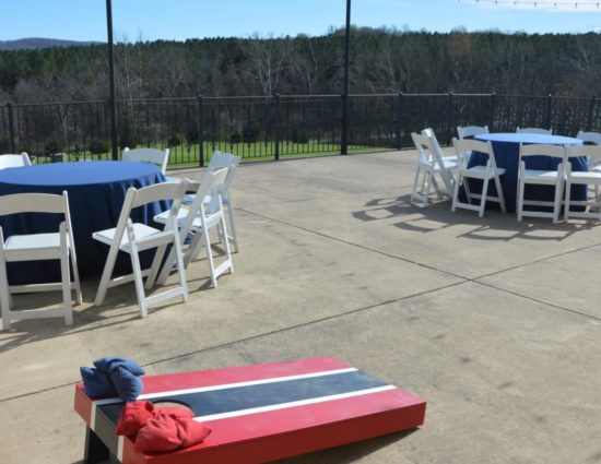 Large concrete patio with two round tables with dark blue tablecloths, white chairs, and a red and blue cornhole board