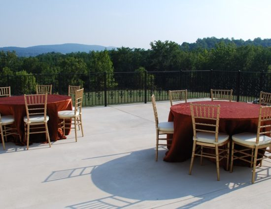 Large concrete patio with two round tables and chairs with copper tablecloths with green trees in the background