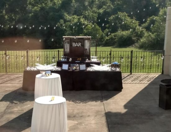 Large concrete patio set up for wedding reception, including a bar station