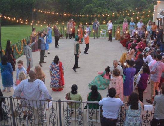 Large wedding party on concrete patio with people watching a group dancing