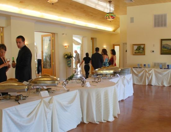 Large room with concrete flooring set up for a wedding reception with white tablecloths and buffet station