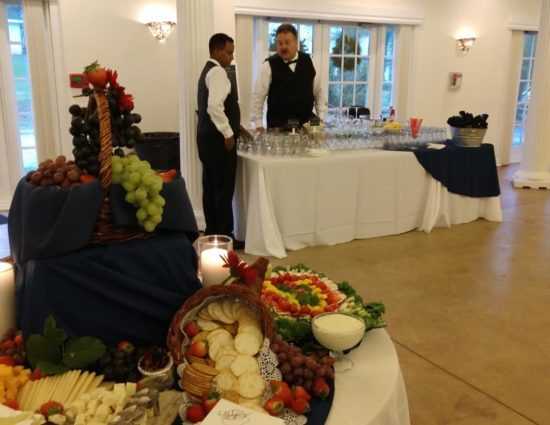 Large room with concrete flooring, large tables with white tablecloths, cheese and crackers station, drink table, buffet table