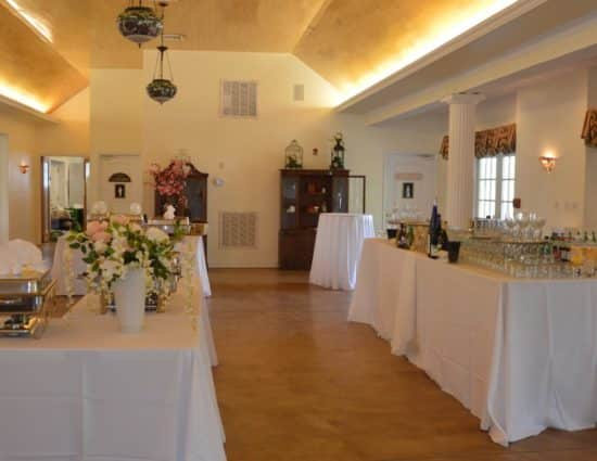 Large room with concrete flooring set up for a wedding reception with white tablecloths, drink station, and buffet station
