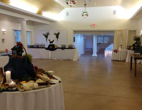 Large room set up for a wedding buffet with a cheese and crackers station, drink station, and buffet station