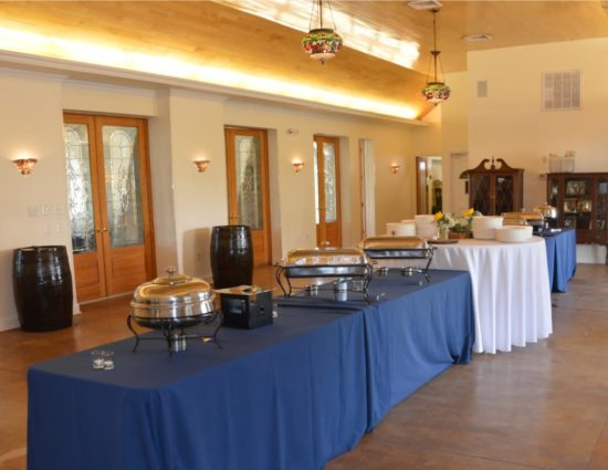 Large room with concrete flooring set up for a buffet with blue and white tablecloths