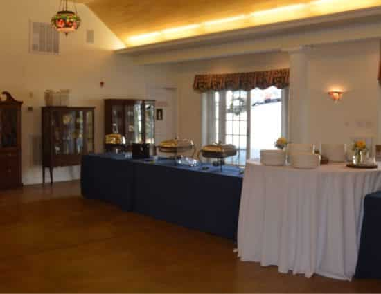 Large room with concrete flooring with buffet tables with navy and white tablecloths