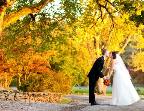 Bride in white dress and groom in black suit standing on gravel path surrounded by trees with green, red, orange, and yellow leaves