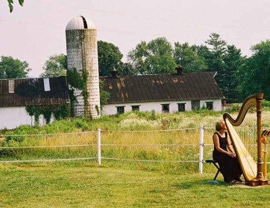 Harp player with black dress sitting near harp with old barn and silo in background