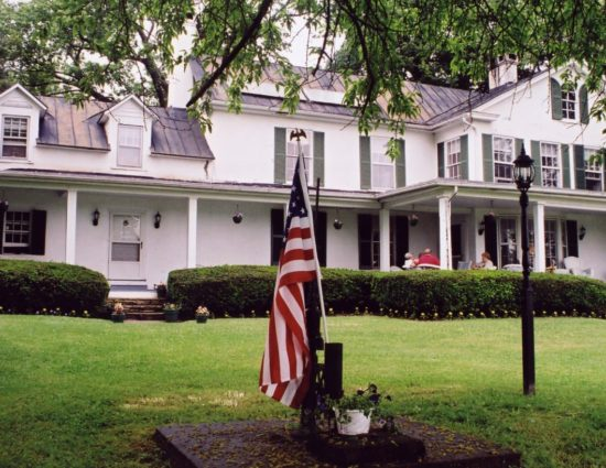 Exterior view of property painted white with green shutters surrounded by green grass and shrubs with American flag out front