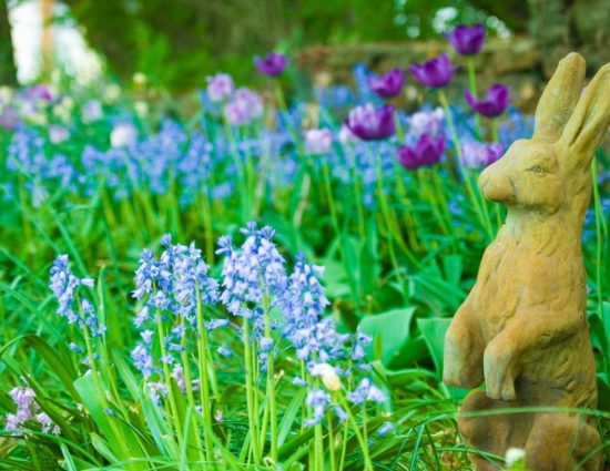 Tan rabbit sculpture sitting in green grasses with blue and purple flowers