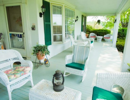Porch with white wicker patio furniture with green cushions
