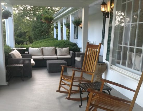Front porch with dark gray wicker patio furniture with tan cushions and two wooden rocking chairs