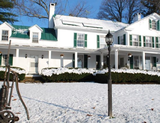 Exterior view of property painted white with green roof and shutters all covered in snow