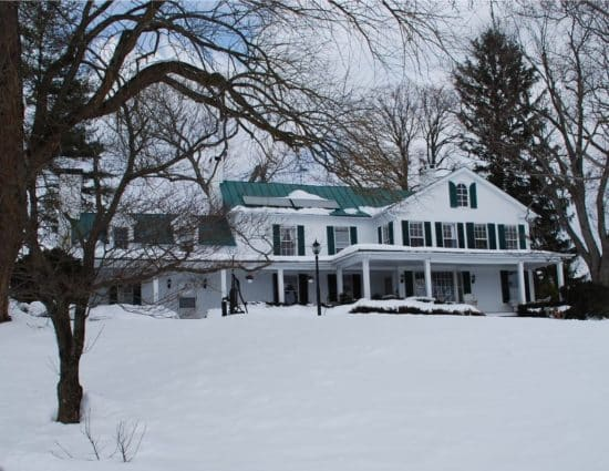 Exterior view of property painted white with green shutters and roof all covered in snow