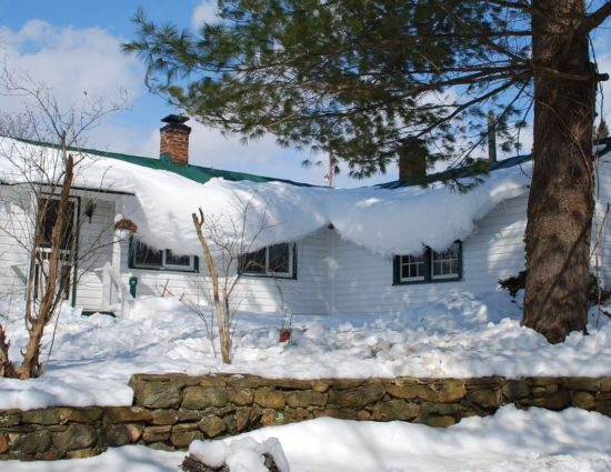 Cottage painted white with green roof covered with snow