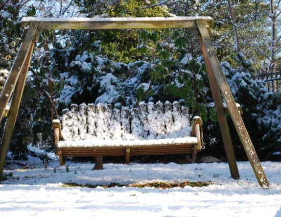 Wooden swing with evergreen trees behind it all covered in snow