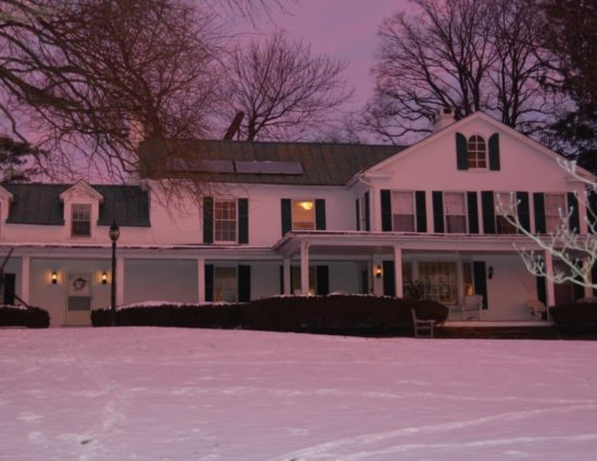 Front of main house painted white with green shutters covered in snow with a light pink hue due to the sun setting