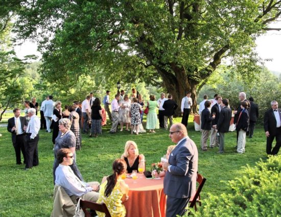 Wedding reception set up on large green lawn near large tree with people sitting at tables and standing around talking