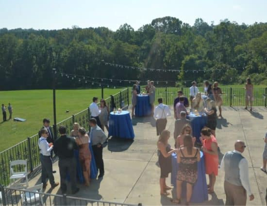 Large concrete patio set up for wedding cocktail reception overlooking large green lawn and green trees