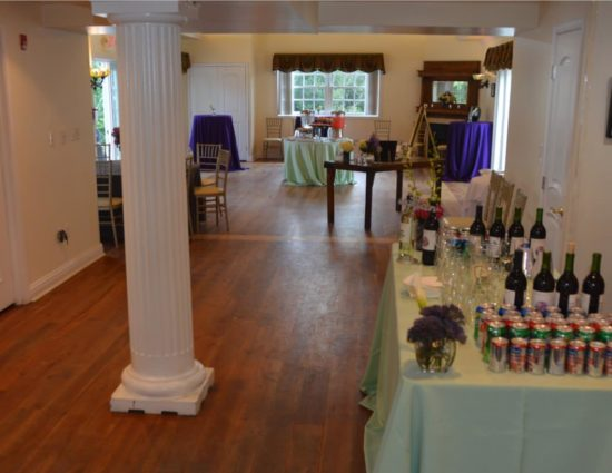 Large room with hardwood flooring set up for wedding reception