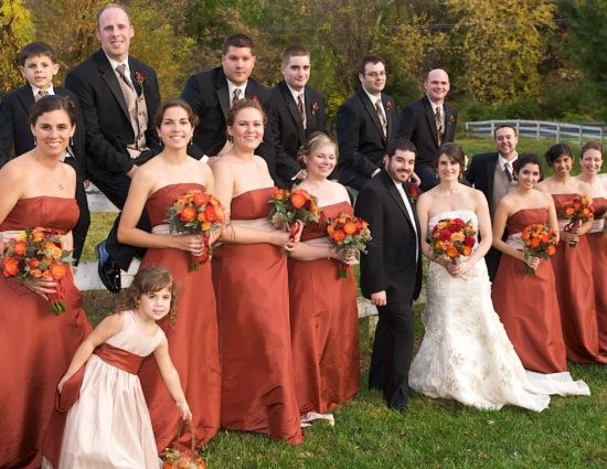 Wedding party in rust colored dresses and black suits with bride in white standing in front of white fence