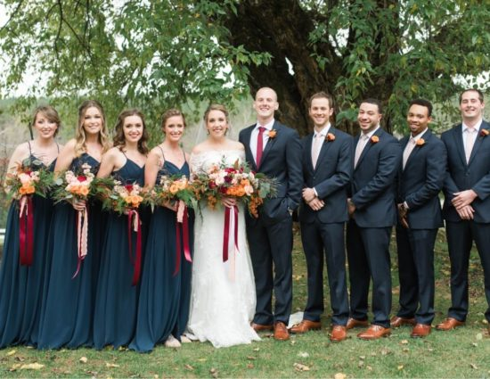 Wedding party in blue dresses and black suits with bride in white standing in front of large tree
