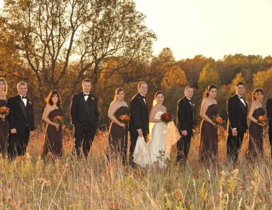 Wedding party in brown dresses and black suits with bride in white standing in a field of grasses with trees in the background with fall color