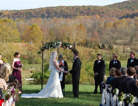 Wedding ceremony outside with trees in the background with fall color and the bride in white dress and groom in black suite at alter