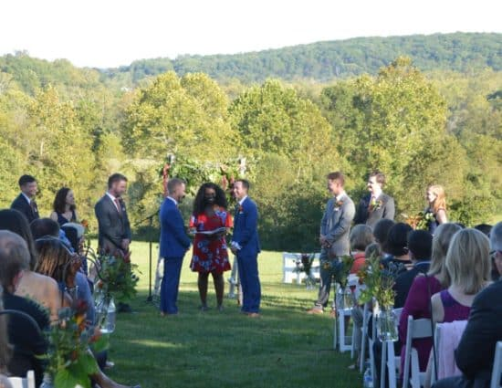 Two grooms in blue suits standing at wedding alter with rolling hills of green trees behind them