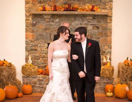 Bride in white dress and groom in black suit standing in front of stone fireplace decorated with bales of hay and orange pumpkins