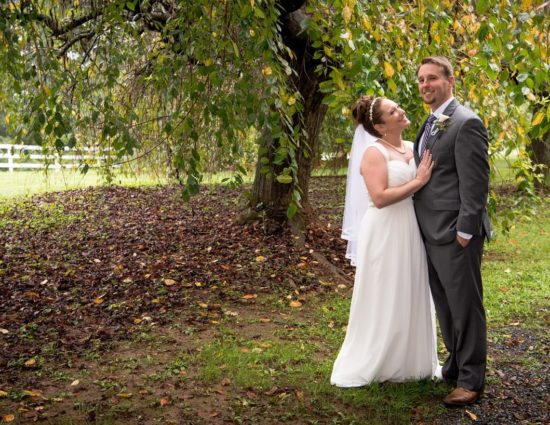 Bride in white dress and groom in gray suit standing under large trees with green leaves