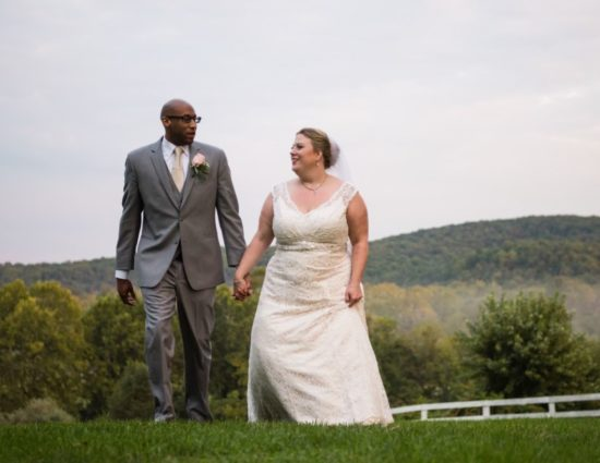 Bride in white dress and groom in gray suit standing in grass with rolling hills behind them