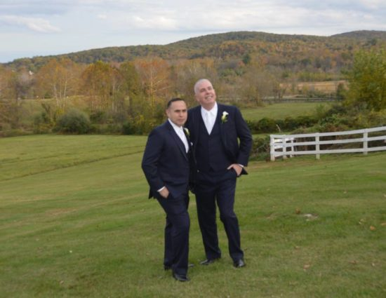 Two grooms in dark navy suits standing in green grass with rolling hills with fall color behind them