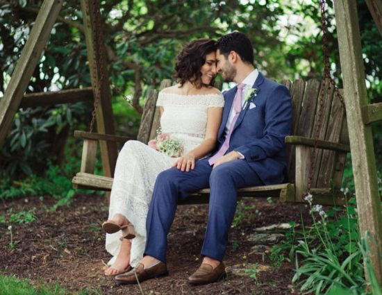Bride in white dress and groom in purple suit sitting on wooden swing