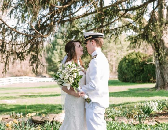 Bride in white dress and groom in white naval uniform standing on stone path surrounded by yellow and white flowers